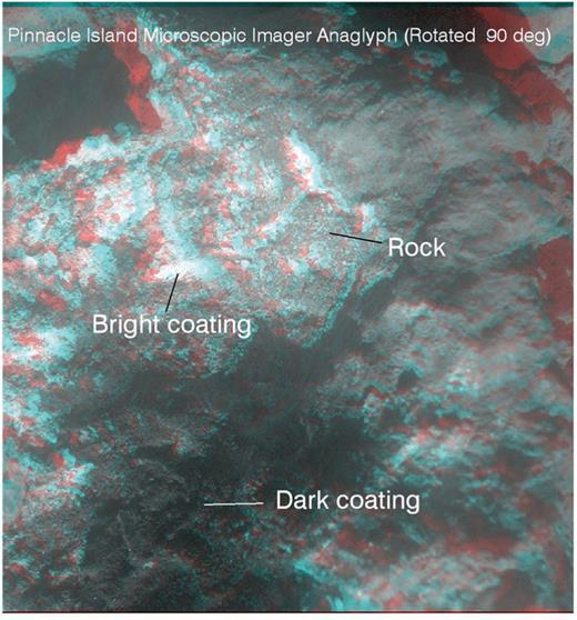 MI-based anaglyph from overlapping stereo coverage is shown for a portion of Pinnacle Island. The coating can be seen directly on top of the rock, with the dark coating occupying the center of the rock and interpreted to overlie the bright coating. The dark coating exhibits a lumpy or popcorn structure. MI product ID 1M442544805IFFCAEOP2955M2F1 and four other MI images were used to construct the anaglyph. Illumination is from the top of the scene.