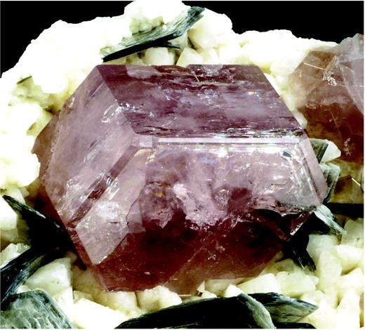 Fluorapatite crystal exhibiting the common forms {001}, {100} and {101} on a matrix of albite and muscovite, from a granitic pegmatite in the Nagar area, Gilgit district, Northern Areas, Pakistan (Jeff Scovil photograph).