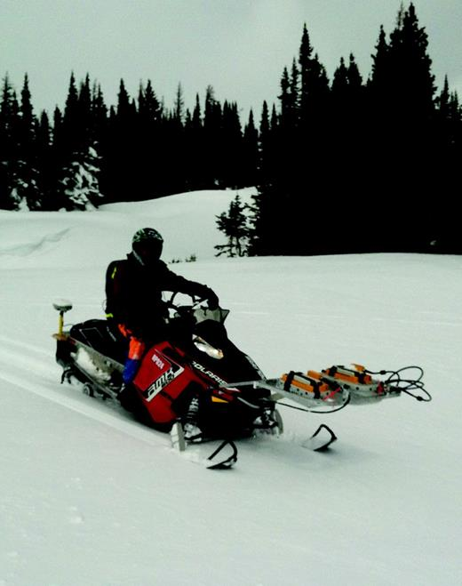 Photograph of the snowmobile-mounted GPR system in use. Two GPR antennas (500 and 800 MHz) are mounted on an aluminum frame attached to the front of the snowmobile. Electronics are carried in the driver's backpack. Locations are logged using the Trimble R8 antenna attached to the rear of the snowmobile.