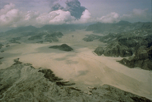 Pyroclastic flow deposit (cream colored) filling 200-m-deep Marella Valley, southwest side of Pinatubo (Philippines) ∼10 km from the vent. Photo courtesy of R.P. Hoblitt, U.S. Geological Survey.