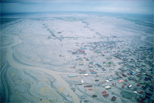 Town of Bacolor, 35 km southeast of Pinatubo (Philippines), buried by an average of 5 m of lahar deposits. In the foreground, roofs are visible; in the background, even roofs are buried. Photo courtesy of C.G. Newhall, U.S. Geological Survey.