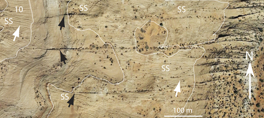 "Google Earth image (Buckskin Gulch, southern Utah; center of image is 37.044°N, 111.988°W) showing widely spaced, straight east-west joints (black arrows) and infilling, curving joints that are closely spaced (white arrows). The closely spaced joints curve to become tangential to the widely spaced joints (lower black arrow). Parallel, convex-up sheeting joints discussed in this paper (Fig. 10) connect many of the closely spaced joints. White line shows the extent of structureless sandstone (SS); ""10"" is the location of rocks shown in Figure 10A."