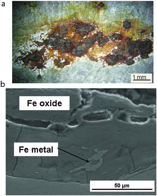 Embedded iron on the surface of the 4 m box; (b) cross-section through the embedded iron, showing the remains of metallic iron in a mass of iron oxide.