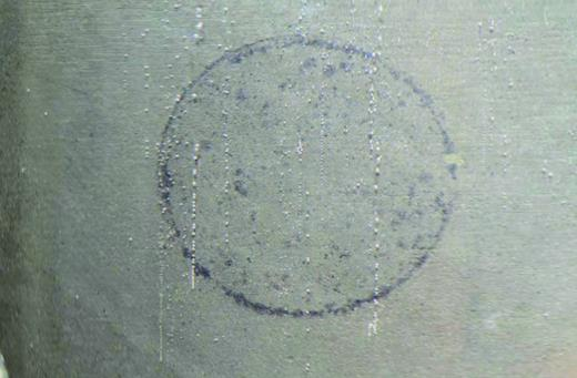 Photograph showing the discharge of gas from the injection face of sample COx-1, following submersion in glycerol and gentle heating (the imprint of the central filter disc is clearly visible in the photo). The discharge of gas was both localized and often episodic, with discrete streams of gas bubbles released following a quiescent periods of inactivity.
