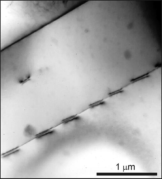 Perth. Bright-field TEM image of inclined dislocations along an Albite twin composition plane in albite in a macroperthite. Each dislocation is associated with a tiny step (a few nm) in the twin plane.