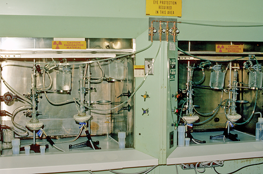 Osmium purifications were originally accomplished by the author using a glass distillation apparatus. The volatile Os tetroxide was generated by mixing dissolved rock with ceric sulphate, then distilling through a water-cooled condenser. Osmium gas was trapped and reduced in an ethanol-hydrochloric acid mixture, chilled by ice. Photo shows mass production set-up in two hoods at the NBS, with 4 stills operating at one time, circa 1987.