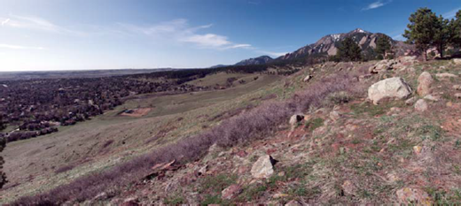 View looking south from Stop 1, along the short trail running east from the parking lot at the National Center for Atmospheric Research. Eastern edge of High Plains is punctuated by smooth, low-sloping surfaces, as in Rocky Flats on the left horizon. Local rivers cut into the Cretaceous shales leave a series of terraces bounding them. South Boulder Creek lies in the middle ground, bounded by at least two other surfaces below Rocky Flats. The surface on which NCAR is built is being eroded from the east by hillslope and small gully systems, exposing coarse clasts in the foreground that mantle the strath surface (photo by R.S. Anderson).