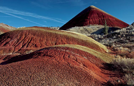 Foreground, use of leading lines, repetition of patterns, and use of the Rule of Thirds—as well as keeping important elements away from the exact center of the image are important compositional elements. A polarizing filter removed scattered light, improving color and clarity, and darkening the sky. Red Hill, The Painted Hills, John Day Fossil Beds. Photo: Ellen Morris Bishop.