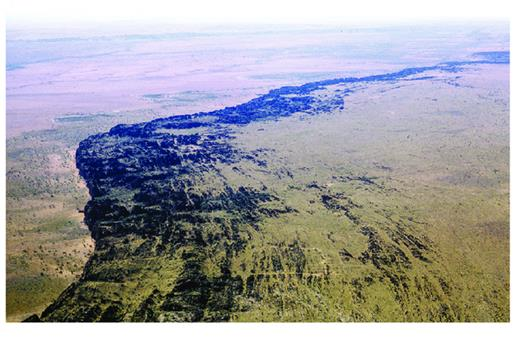 —Aerial view looking east over the northeast side of the Oscar Range. Morown Cliff, at the north-facing front of the range, is essentially the exhumed late Famennian reef scarp. Note linear corridors following neptunian dykes, parallel to the reef front, with a subsidiary fracture system at right angles to those dykes.